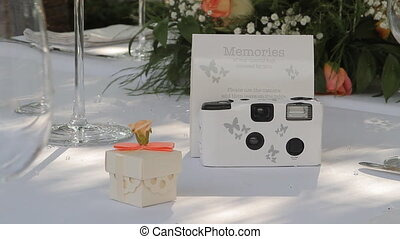 Disposable white wedding camera on a wedding table.
