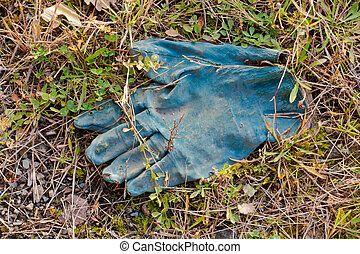 Disposed blue protective rubber glove slowly decomposing...