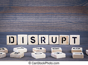 Disrupt word written on wood block. Dark wood background with texture