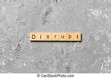 DISRUPT word written on wood block. DISRUPT text on cement table for your desing, concept