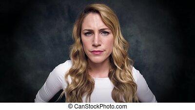 Dissatisfied blonde on a dark background. 4K video.