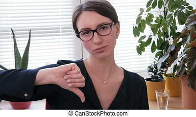Dissatisfied businesswoman looking into camera and showing...