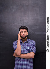 Dissatisfied casual man is on blank chalkboard background