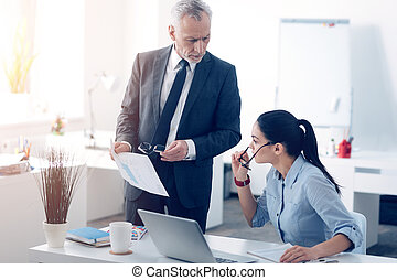 Dissatisfied chief carping at business document with his office worker