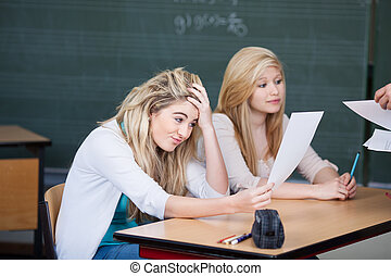 Dissatisfied female student looking at question paper while professor giving paper to classmate at desk