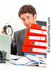 Dissatisfied modern businessman sitting at office desk with pile of folders and holding alarm clock in hand