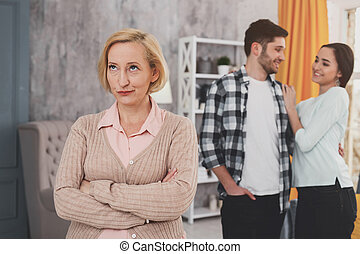 Dissatisfied senior woman standing at home - The third odd ...
