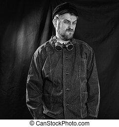 dissatisfied welder in black boilersuit