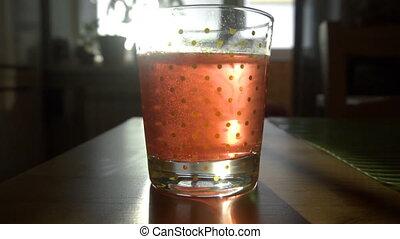 Dissolving Aspirin fizzy pill in glass of water -...