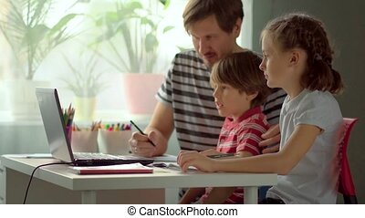 Distance learning for children at home. Father explains school material to daughter and son with a laptop.