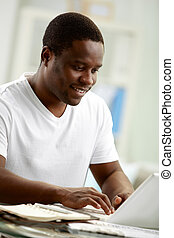 Distance learning - Image of young African man typing on...
