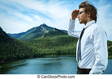 distance - Successful business man standing on a peak of the...