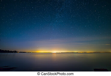 Distant City Lights With Stars and Water
