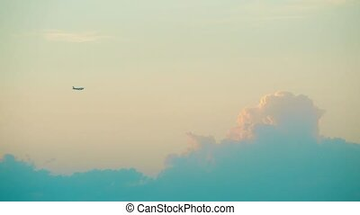 Distant commercial airplane flying against beautiful sunset clouds