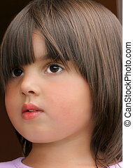 Face of a little girl with a distant look in her eyes.