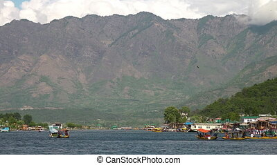 Distant mountains above boaters in Dal lake - Wide shot of...