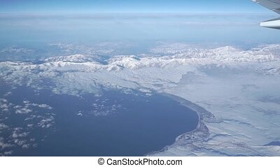 Distant mountains and sea beneath the airliner. Aerial video...