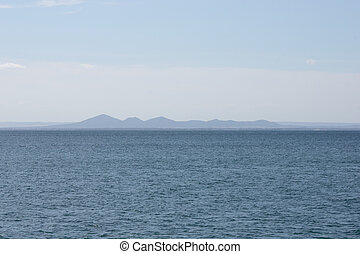 Distant mountains from across a rippled ocean