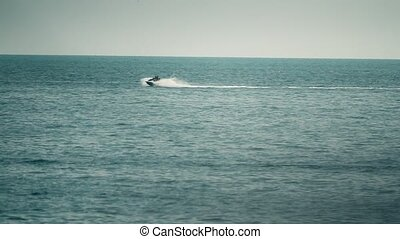 Distant people riding jet ski at sea, slow motion shot -...