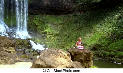 lady sits on rock changing yoga position by waterfall -...