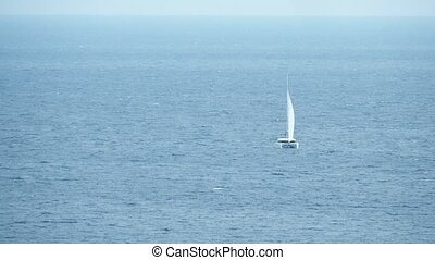 Distant sailing catamaran at sea, long shot