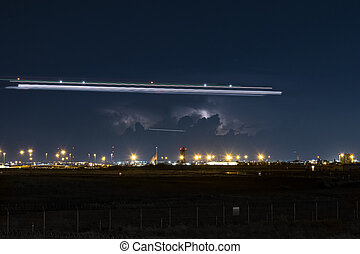 Distant thunderstorm and night trails over airport at night