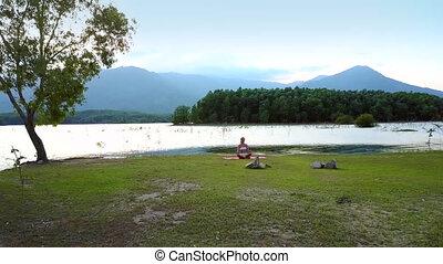 distant view girl changes yoga pose on lake bank