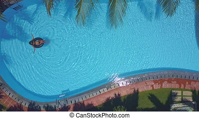 distant view through palm leaves on pool with lady -...