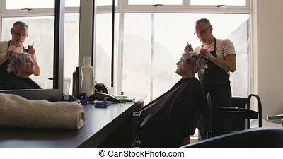 Alternative cool hair salon. Side view of a Caucasian male hairdresser working in a hair salon, holding brush, colouring hair of a Caucasian female client in slow motion