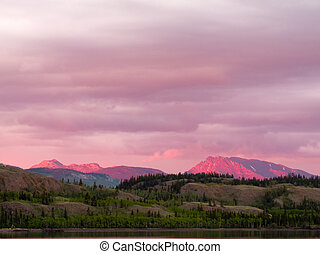 Distant Yukon mountains glowing in sunset light - Distant...