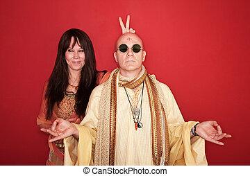 Woman with peace sign or bunny ears over meditating Guru's head