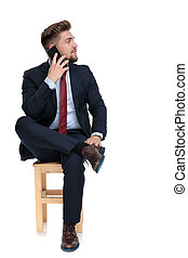 distracted young businessman talking on the phone in studio