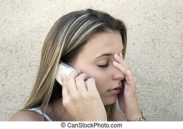 A distressed young woman on the phone.