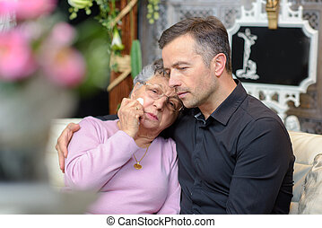 Distressed elderly lady leaning head on young man's shoulder