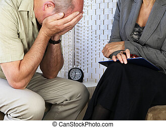 Female counselor with distressed male patient holding head in hands seated