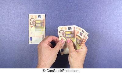 distributing 50 euros banknotes - man hand distributing 50...