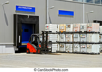 Forklift vehicle in front of cargo doors at distribution warehouse