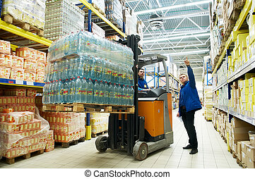 worker and manager distributing goods in a warehouse with forklift truck loader