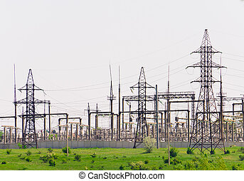 Distribution of electricity sub-station. Power transmission towers on the hill