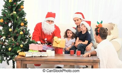Distribution of gifts by Santa Claus to a family