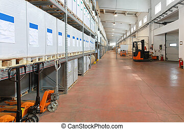 Distribution warehouse with shelves and forklifts in long ...