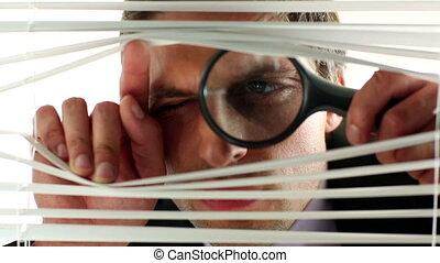 Distrustful businessman using magnifing glass