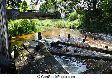 Disused mill near river at summer