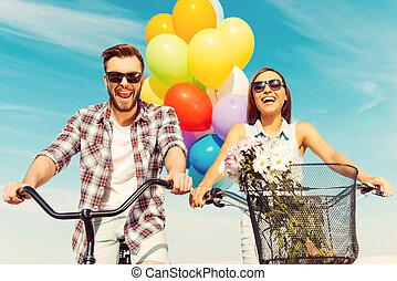 dit, is, zo, veel, fun!, laag hoek overzicht, van, vrolijk, jong paar, het glimlachen, en, paardrijden, op, bicycles, met, kleurrijke ballons, in, de, achtergrond
