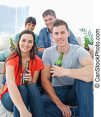 divan, couple, amis, asseoir, une, plancher, autre, sourire, groupe, bières