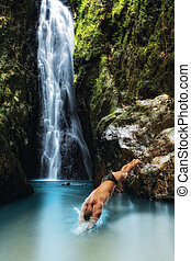 portrait of young man diving in tropical waterfall