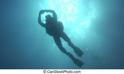A scuba diver moves with slowly kicking fins through the blue water.