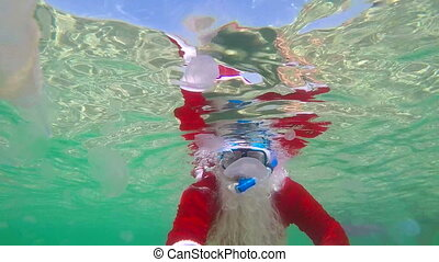 Diver dressed as Santa Claus on Christmas day swimming under...