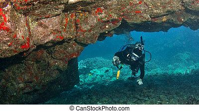 Diver exploring a Lava Arch in Hawaii - Diver exploring a...