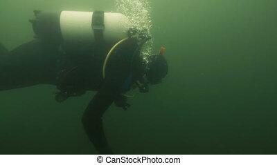 Diver in diving equipment swimming under water river. Underwater diving